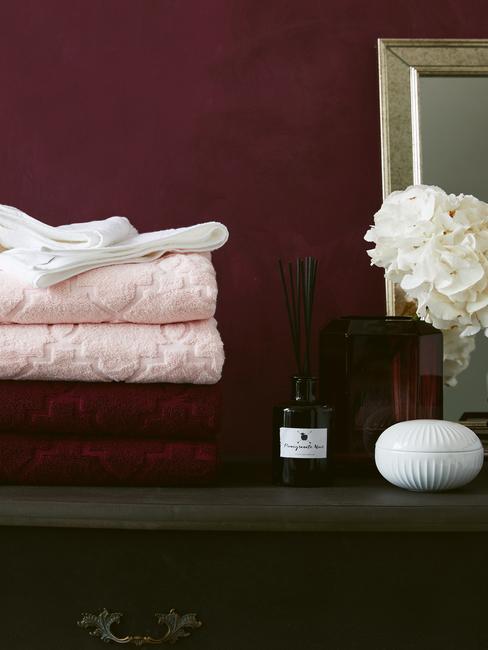 Bordowa łazienka z ręcznikami, kwiatami i mydelniczką