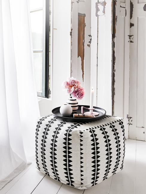 Biało-czarny puf z czarną tacą, świeczkami oraz kwiatami