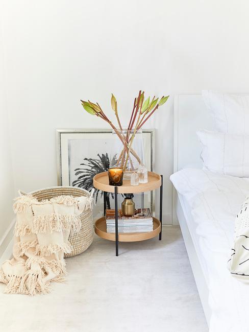 Okrągły stolik nocny z rośliną, kosz rattanowy stojący przy łóżku
