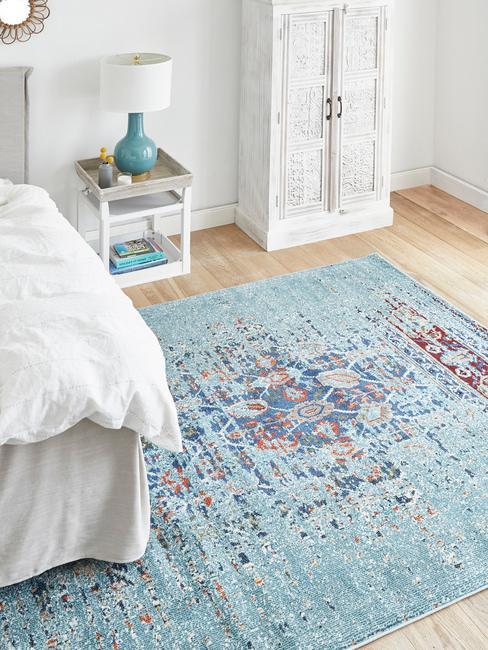 Fragment sypialni z niebieskim dywanem, stolikiem nocnym ora białą szafą