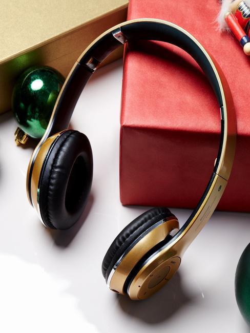 Złote słuchawki leżące na czerwonym pudełku prezentowym