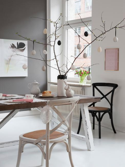 Drewniany stoł z wazonem z gałązkami, na których wiszą ozdobne jajka