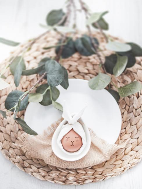 Dekoracja stołu wielkanocnego z użyciem białego talerza, jajka oraz roślin