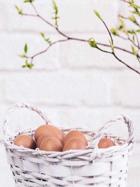 Biały koszyczek wielkanocny z jajkami pod gałązką