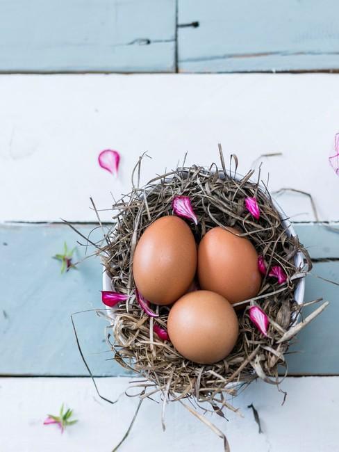 Koszyk wielkanocny zrobiony z gałązek, w któym znajdują się jajka