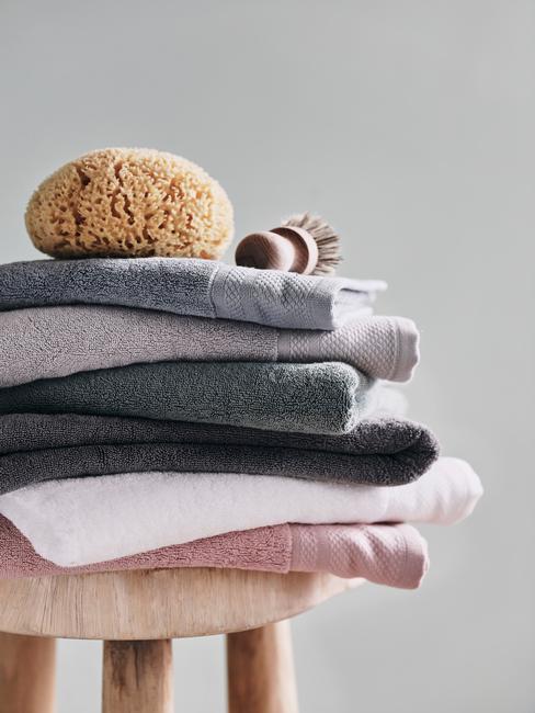 Ręczniki w szarościach i pudrowym różu poukładane na drewianym taborecie