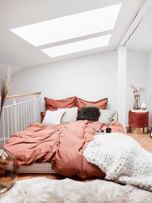 Biała sypialnia na poddaszu z czerwoną pościelą, pledowym kocem oraz pufem