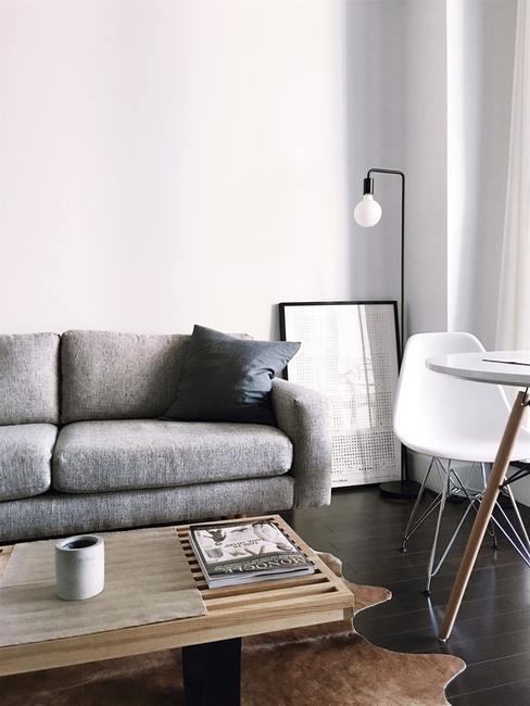 Salon z szarą kanapą, drewnianym stolikiem kawowym, lustrem oraz krzesłem ze stołem