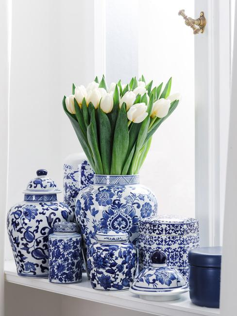 Zbliżenie na parapet na którym znaduje się biało-niebieska porcelana oraz białe tulipany