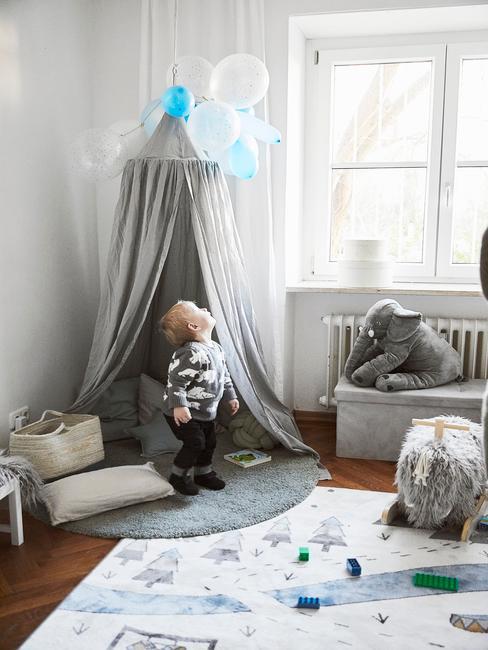 Chłopczyk stojący w pokoju dziecięcym z szarym namotem, dywanem we wzory oraz z zabawkami
