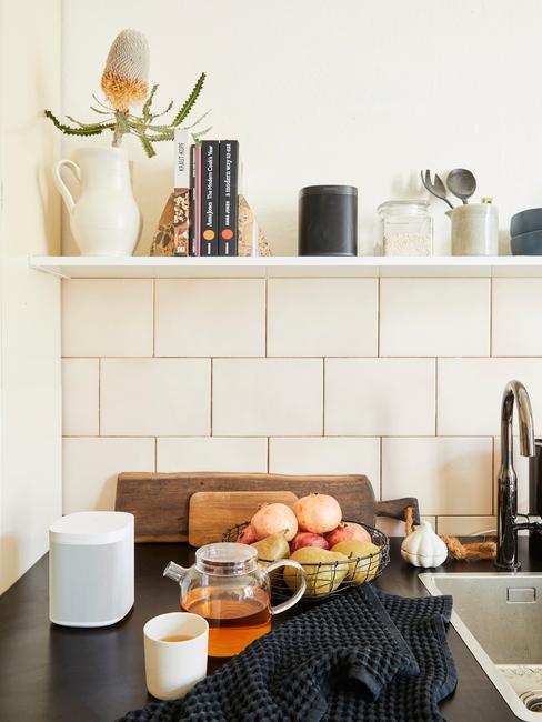 Fragment kuchni z białymi kafelkami, półką ścienną oraz owocami na stole