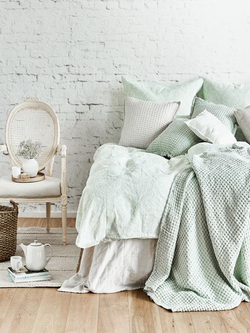 Biała sypialnia z ceglaną ściąną, łóżkiem oraz krzesłem