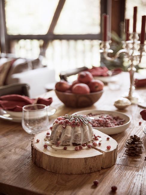 Udekorowany, drewniany stół, na kórtym stoi patera wykonania z pnia drzewa