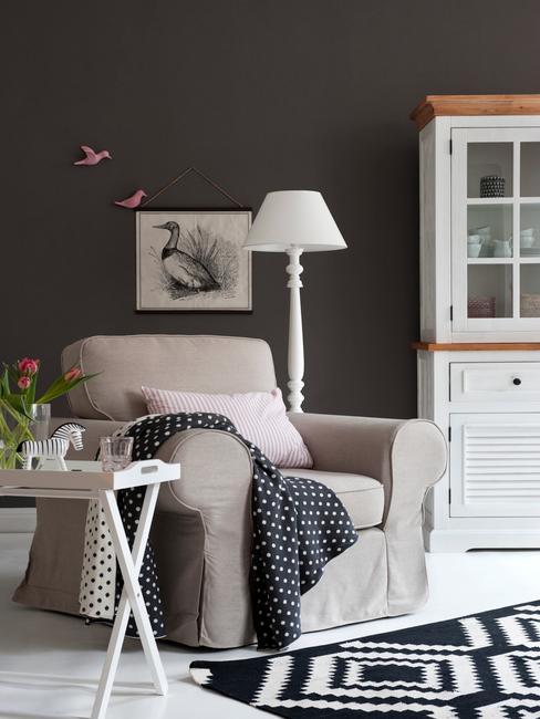 Salon w kolorze antracytu z beżowym krzesłem, białym kredensem oraz białą lampą