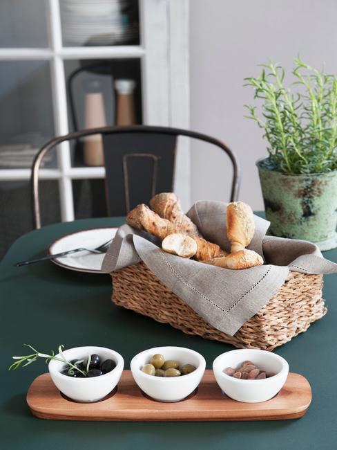 Czarny stół na któym jest umieszczony kosz pieczywa oraz deska z trzema rodzajami oliwek