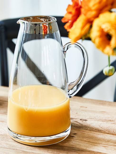 Dzbanek z sokiem pomarańczoym sotjący na drewnianym blacie obok kwiatów
