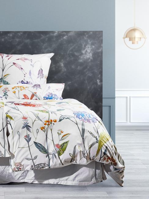 Łóżko w sypialni z pościelą w kwiaty oraz zagłówkiem wykonanym z czarnego marmuru