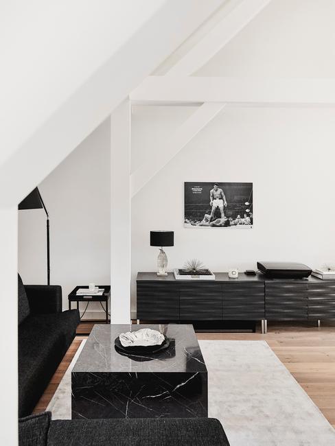 Minimalistyczny czarno-biały pokój z czarną sofą, stolikiem z czarnego marmuro oraz komodą