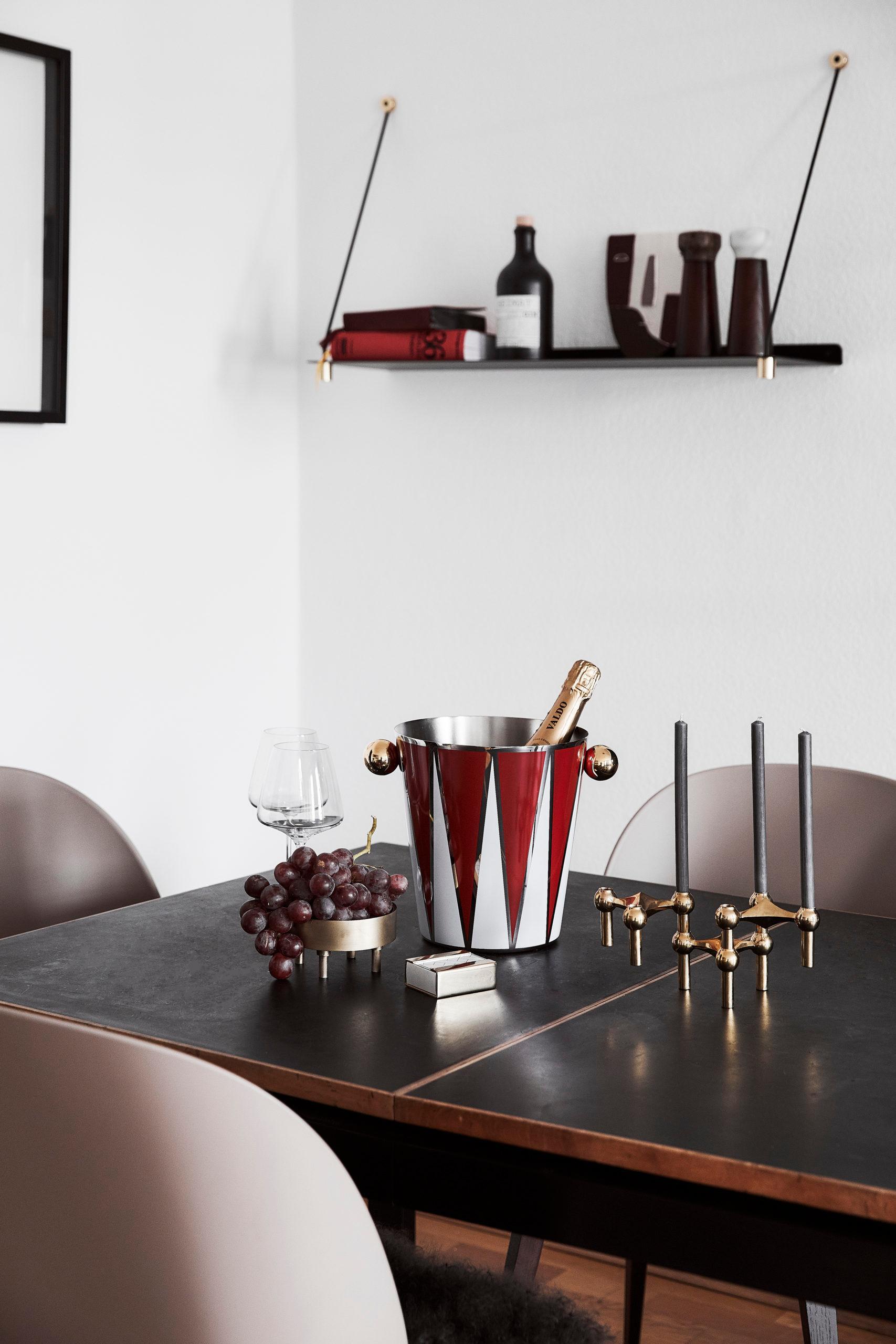 Biała jadania z czarnym stołem, brązowymi krzesłami oraz półką ścienną