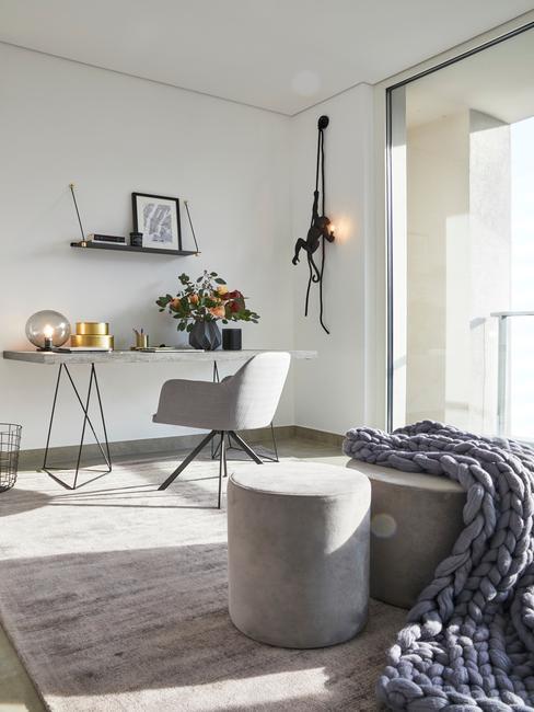 jasne pomieszczenie z biurkiem, szarnym potelem, pufem, dywanem oraz półką ścienną