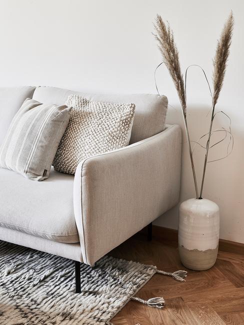 Szara kanapa w stylu boho z poduszkami, wazon z trawą pampasową oraz czarno-biały dywan