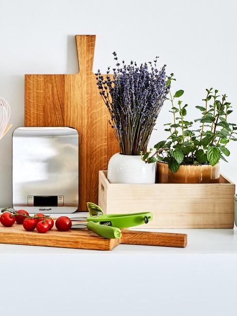 Fragment blatu kuchennego z deskami do krojenia oraz skrzynką z ziołami oraz lawenda w doniczce