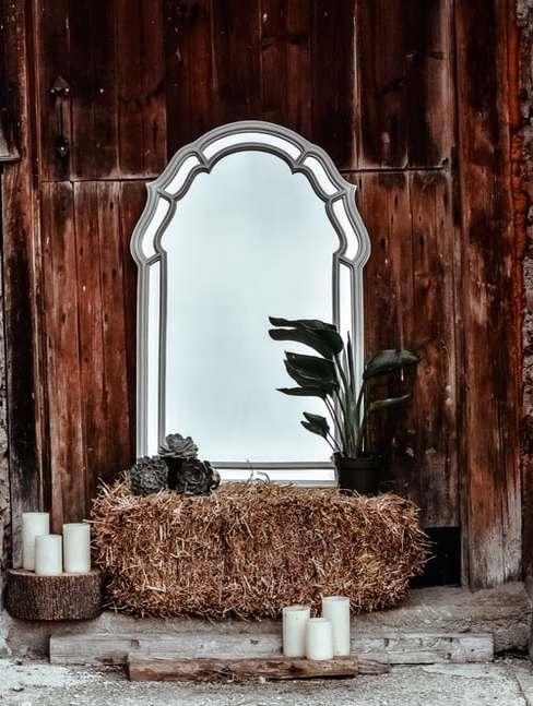 Fragment dewnianej sali weselnej z lustrem, roślinami, świecami oraz stosem siana