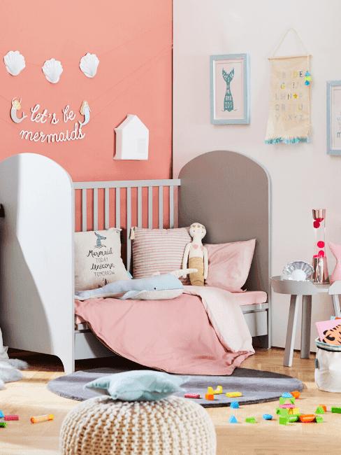 Pokój dziewczyny z różową ścianą, łóżeczkiem oraz zabawkami