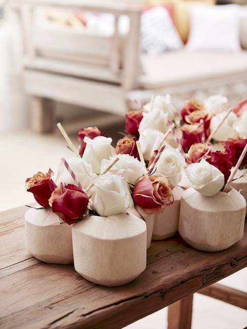 Drinki z kokosie udekorowane białymi i czerwonymi różami na drewnianym stole