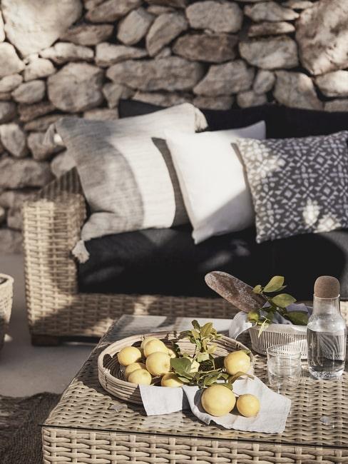 Rattanowe meble tarasowe, dekoracyjne poduszki i taca z cytrynami