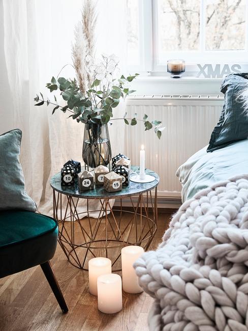 Zbliżenie na stolik pomocniczy w sypialni, na którym znajduje się bukiet kwiatów oraz świeczki