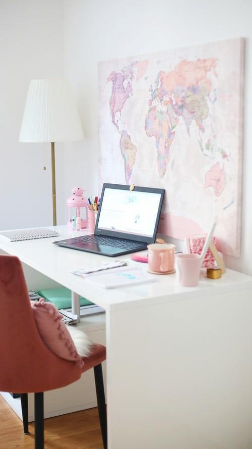 Biały pokój z białtym biurkiem oraz różowym przesłem oraz pastelowo różowymi dekoracjami