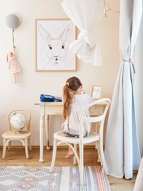 Dziewczynka siedząca przy biurku w pokoju dziecięcym z obrazkiem na ścianie