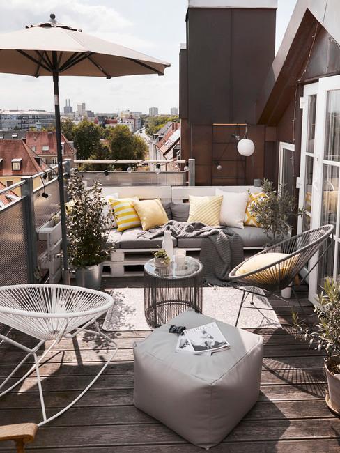 Taras na dachu z meblami w odcianiachszarności, żółtymi poduszkami oraz parasolem