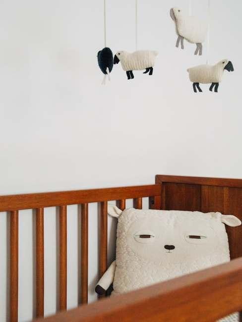 Drewniane łóżeko z poduszką oraz zabawkami w kształcie owieczek