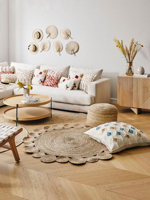 Salon boho z jasną kanapą, drewnianym stolikiem kawowym, wachlarzami na ścianie, komodą z wazonem trawy pampasowej oraz plecionymi dywanmi