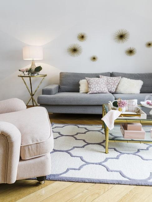 Salon w stylu glam z sofą, fotelem oraz metalowymi dekoracjami na ścianie