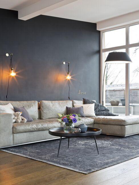 Jasna sofa i stolik kawowy na tle antracytowej ściany w salonie