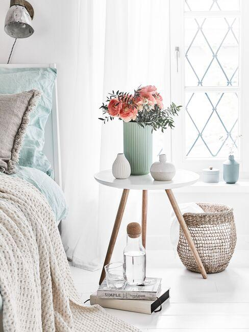 Miętowy wazon z kwiatami na stoliku pomocniczym w sypialni