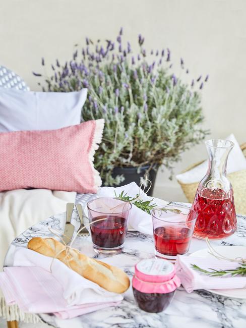 Fragment tarasu z sofą ogrodową z poduszkami, drinkami oraz dużą doniczką lawendy