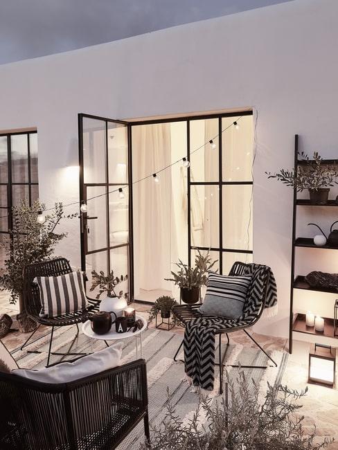 Taras z meblami i dekoracjami ogrodowymi w biało-czarnym barwach