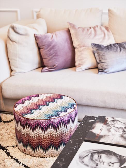 Fargment salonu z beżową kanapą, poduszkami dekoracyjnymi oraz wzorzystym pufem