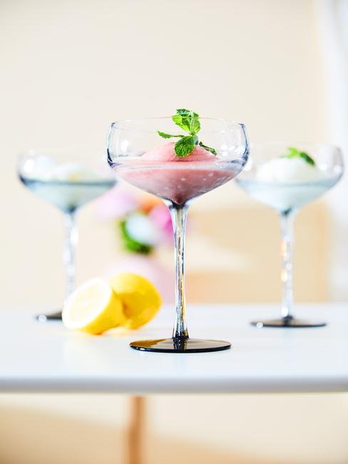 Trzy szklane kieliszki do martini z lodami