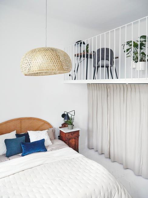 Biała sypialnia z łóżkiem oraz antresolą, na której znajduje się domowe biuro