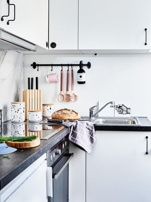Mała, biała kuchnia w bloku z czarnym blatem oraz przyborami kuchennymi