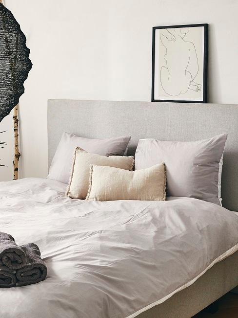 Sypialnia z łożkiem o szarym zagłówku, poduszkami oraz czarnymi dekoracjami