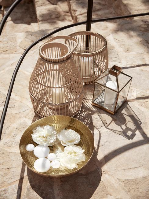 Lampiony ze świecami wykonane z bambusa oraz misa dekoracyjna z kwiatami