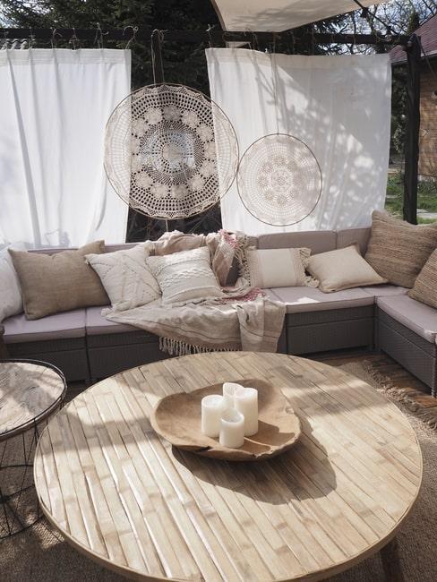 Sofa ogrodowa z dużą ilością poduszek dekoracyjnych, w tle ł