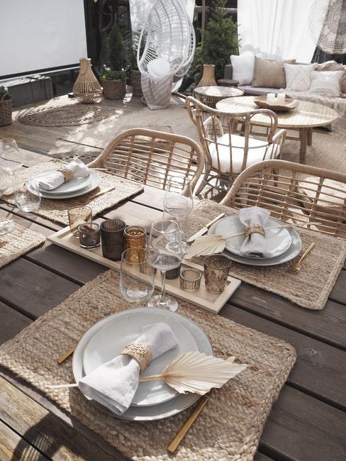 Stół nakryty w stylu boho: słomine podkładki, serwetki i taca ze świecami.
