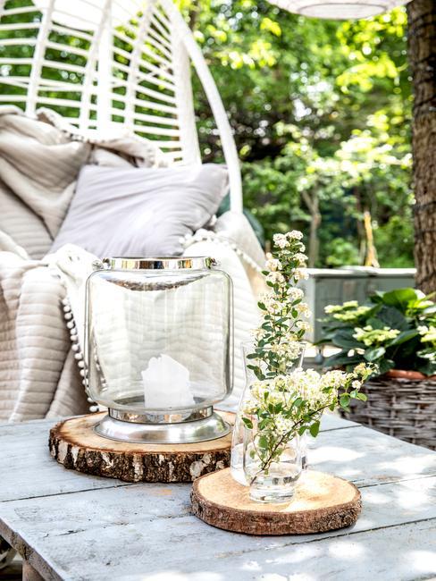 Lampion ze słoika postawiony na stoliku zrobionym z palet